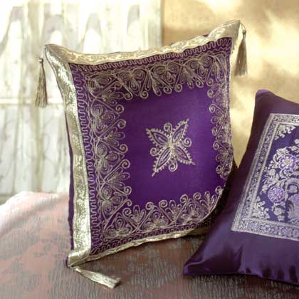 Purple Throw Pillow With Gold Embroidery And Tassles. Made With 60% Lurex,  20% Polyester, And 20% Nylon Material. Recommend Dry Clean Only.